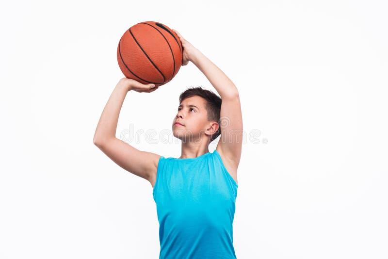 Jeune garçon jouant le basket-ball d'isolement sur le blanc photographie stock