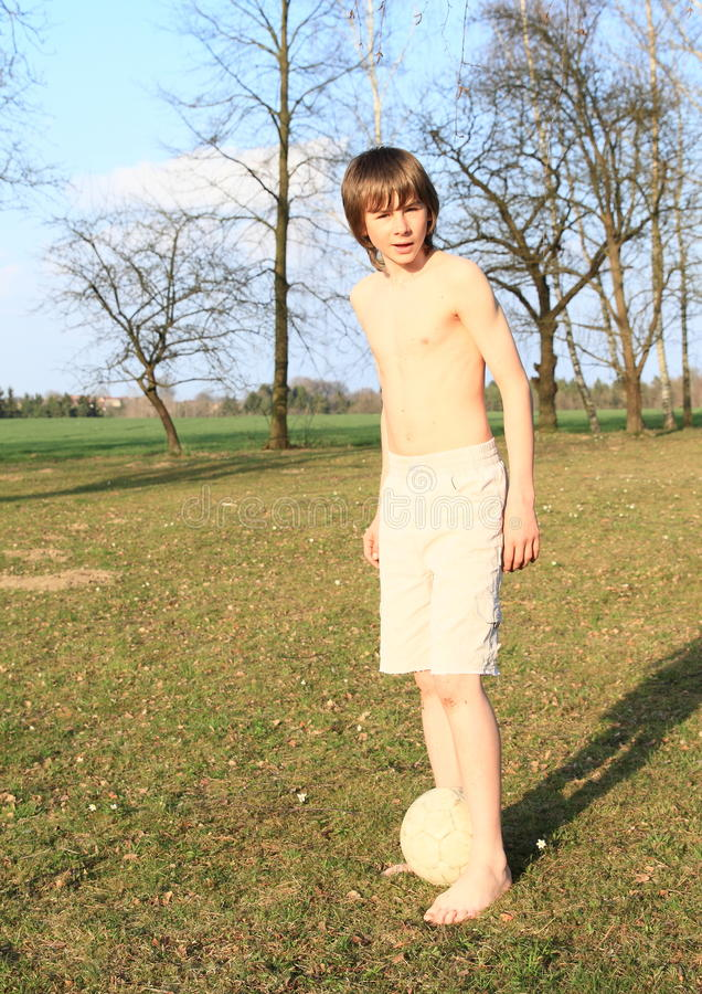 Jeune garçon jouant le football nu-pieds photo stock
