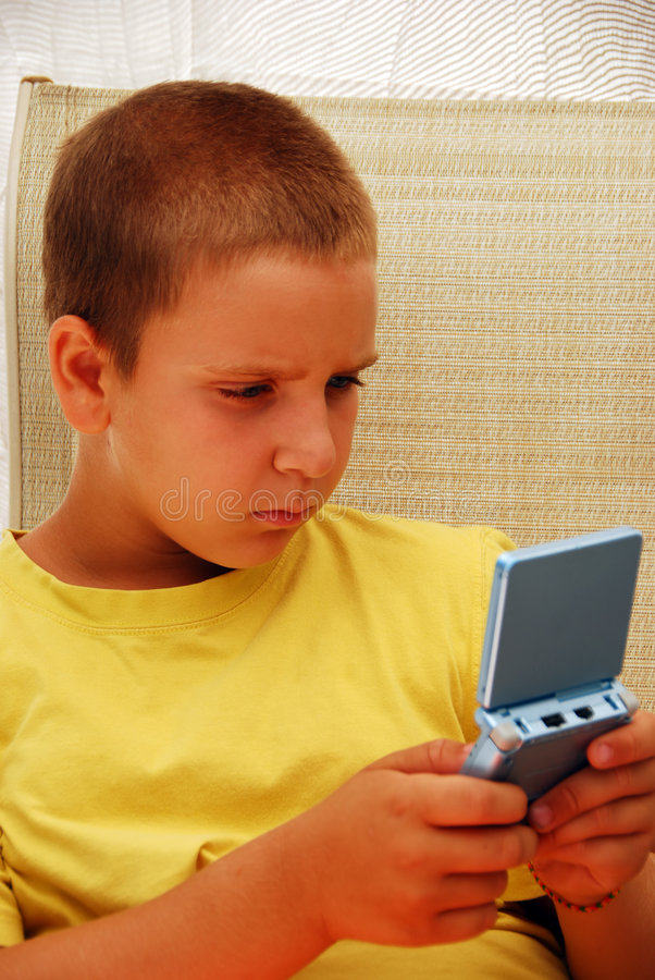 Jeune garçon jouant le jeu vidéo image stock
