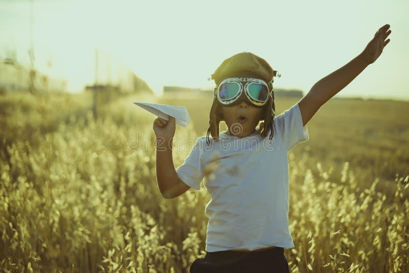 Jeune garçon jouant pour être pilote d'avion, type drôle avec l'aviateur c photo libre de droits