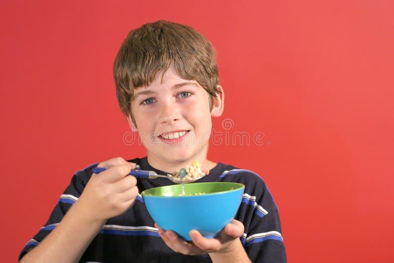 Jeune garçon mangeant de la céréale photographie stock