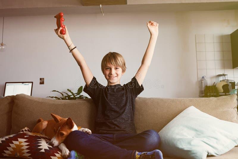 Jeune garçon mignon célébrant sa victoire dans la console de jeu vidéo posée sur un sofa avec le chiot de chien de basenji dorman photographie stock libre de droits
