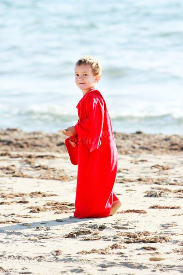 Jeune garçon mignon dans le grand T-shirt sur la plage de sable photo libre de droits