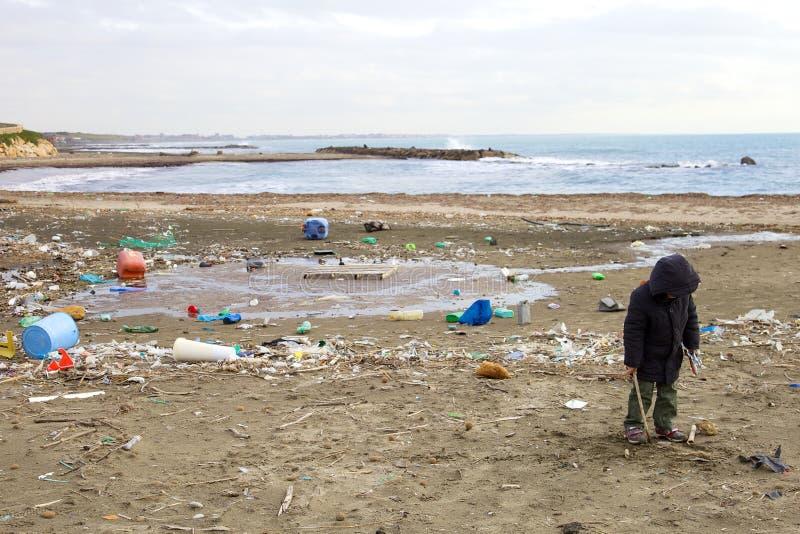 Jeune garçon ne s'inquiétant pas de la saleté et du danger de la plage polluée images stock