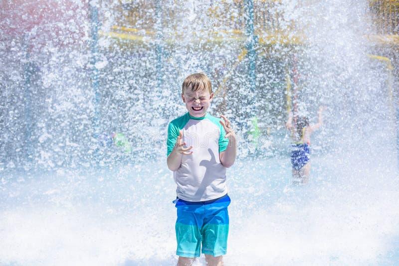 Jeune garçon obtenant le trempage humide tandis qu'à un parc aquatique extérieur photos libres de droits