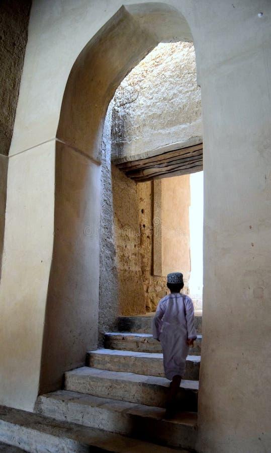 Jeune garçon omanais entrant dans le fort de Bahla, à l'ouest de Nazwa, l'Oman images stock