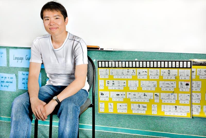 Jeune gar?on ou scientifique s'asseyant sur une chaise et un sourire photographie stock libre de droits