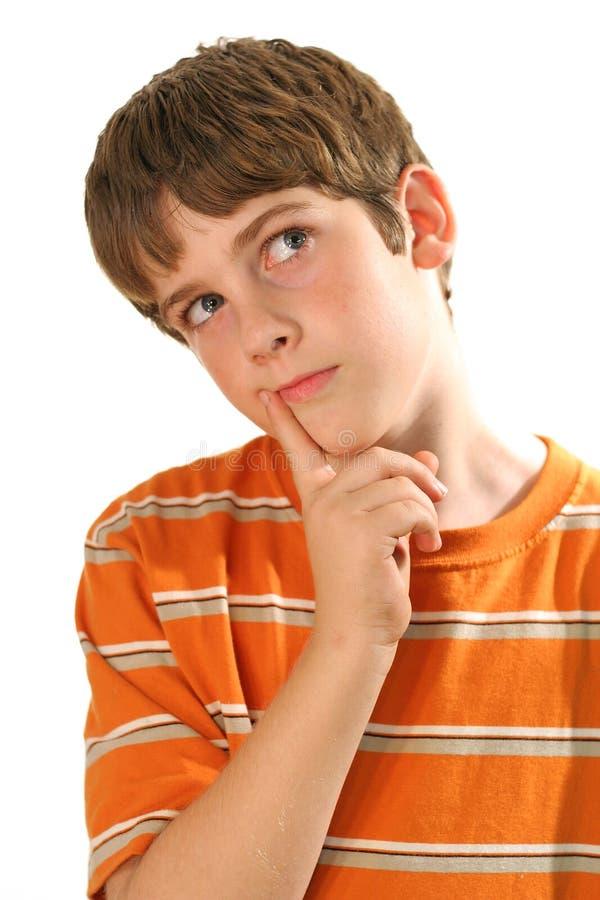 Jeune garçon pensant sur le blanc - verticale image stock