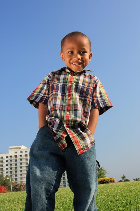 Jeune garçon posant sur l'herbe images stock