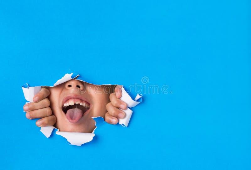 Jeune garçon poussant sa langue par un trou déchiré à l'arrière-plan de papier photos libres de droits