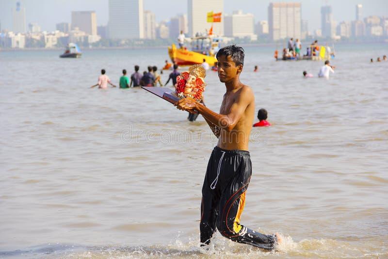 Jeune garçon prenant l'idole de Ganapati pour l'immersion, Ganapati visarjan, Girgaon Chowpatty photo libre de droits