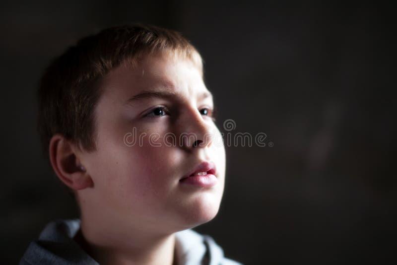 Jeune garçon recherchant avec espoir dans ses yeux photo libre de droits