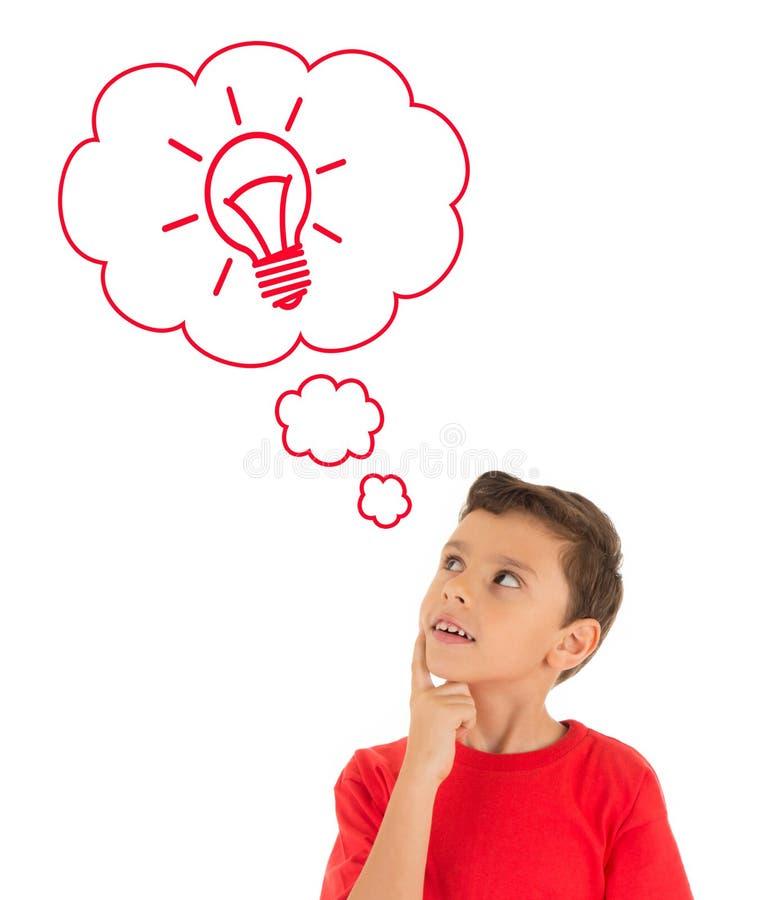 Jeune garçon recherchant et pensant avec l'ampoule dans les bulles photos libres de droits