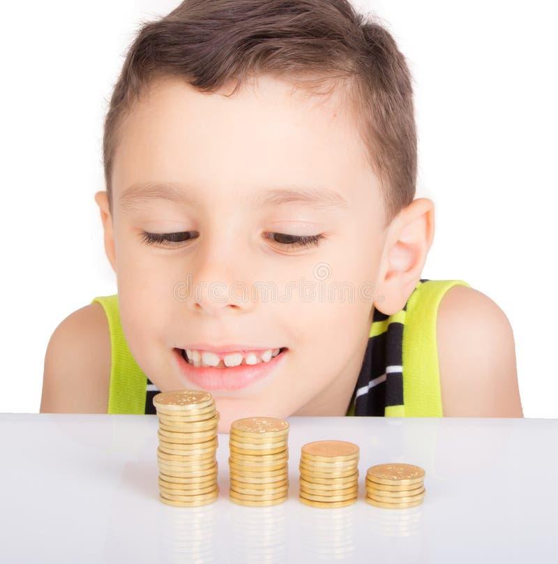 Jeune garçon regardant à ses pièces de monnaie images stock