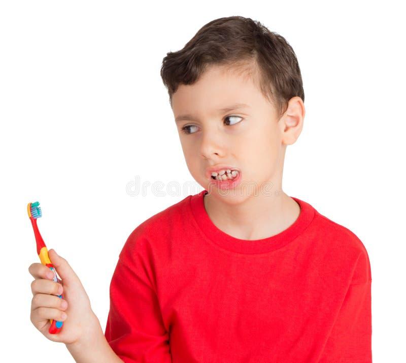 Jeune garçon regardant de la manière fâchée à sa brosse de dents photographie stock