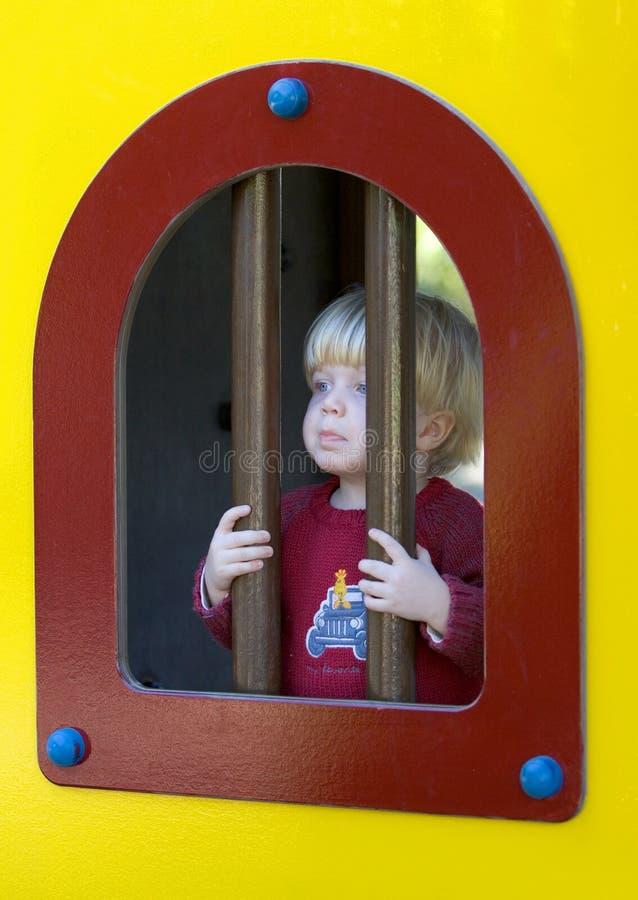 Jeune garçon regardant par des bars d'un hublot dans une cour de jeu de gosses photo stock
