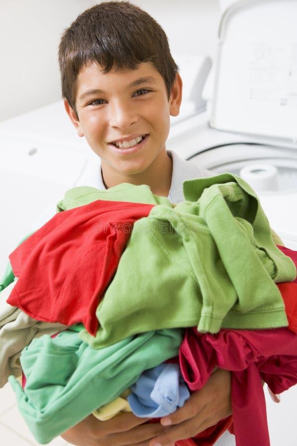 Jeune garçon retenant une pile de blanchisserie photo stock