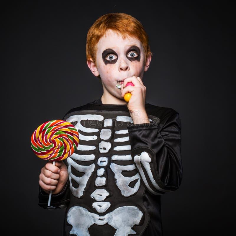 Jeune garçon rouge heureux de cheveux avec le costume squelettique tenant et mangeant les sucreries colorées image libre de droits