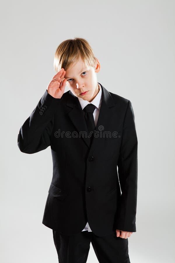 Jeune garçon sérieux dans la salutation noire de procès photos stock