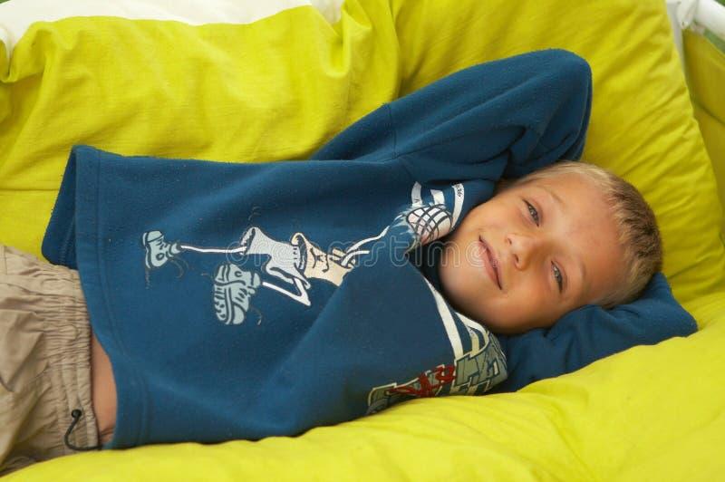 Jeune garçon s'étendant sur des oreillers photos libres de droits