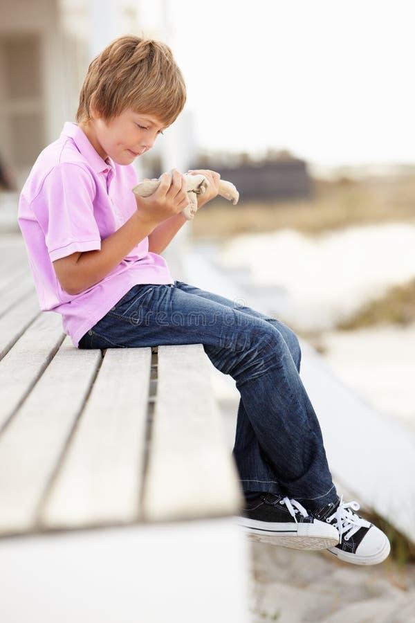 Jeune garçon s'asseyant à l'extérieur retenant des étoiles de mer photos stock