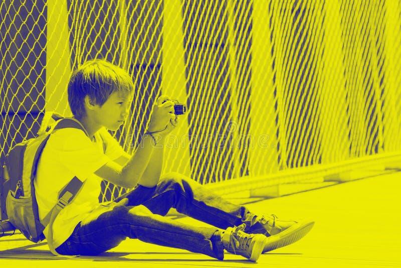 Jeune garçon s'asseyant avec un appareil photo numérique et prenant des photos dans la rue effet de duotone images stock