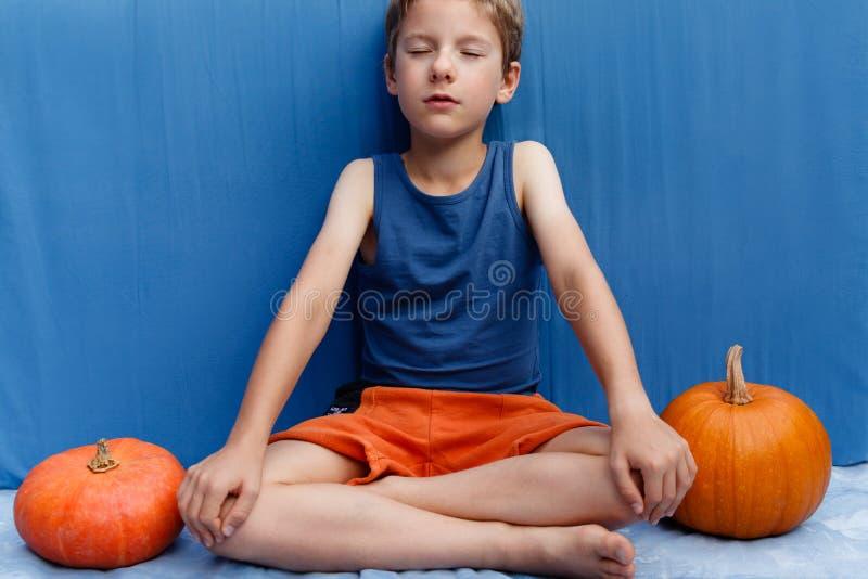 Jeune garçon s'asseyant dans la pose de yoga sur le fond bleu avec des potirons Halloween coloré ou conception saine de mode de v photo libre de droits
