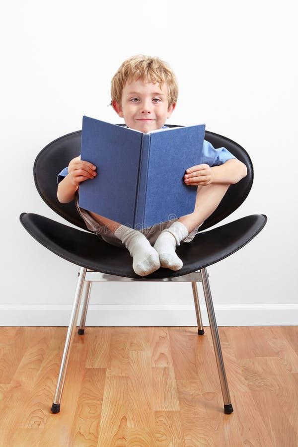 Jeune garçon s'asseyant dans une présidence affichant un livre photos libres de droits