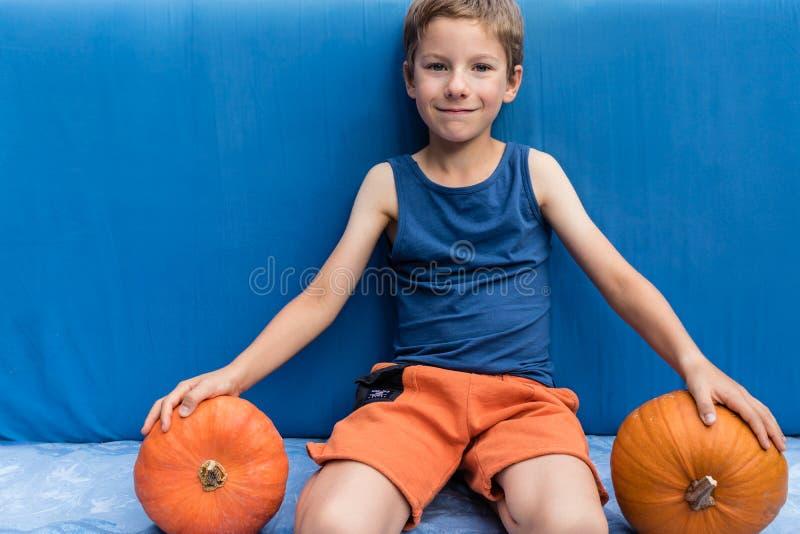 Jeune garçon s'asseyant sur le fond bleu avec des potirons Halloween coloré ou conception saine de mode de vie images libres de droits