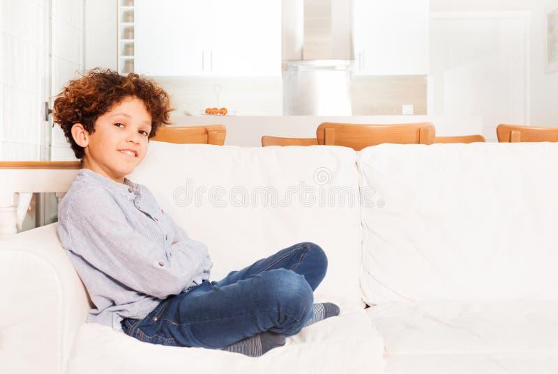 Jeune garçon s'asseyant sur le sofa dans la salle de salon photos libres de droits