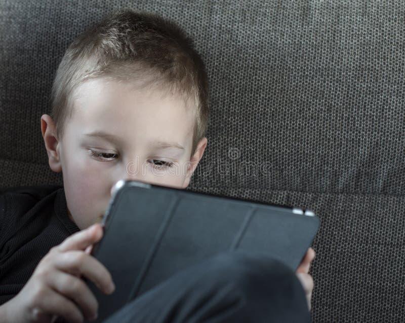 Jeune garçon s'asseyant sur le sofa dans le salon et les bandes dessinées de observation sur le comprimé Portrait d'un enfant fut photo stock