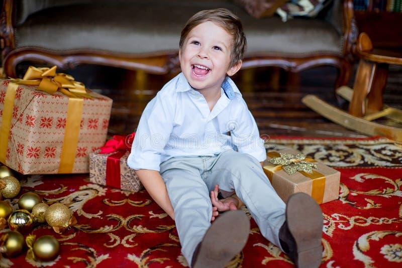 Jeune garçon s'asseyant sur le tapis avec des cadeaux de Noël photographie stock libre de droits