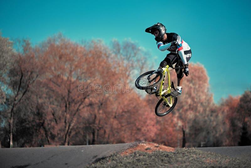Jeune garçon sautant avec son BMX Bike à la piste de pompage image stock