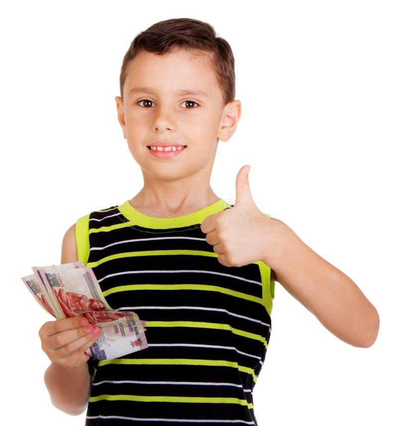 Jeune garçon signant heureusement tenir CORRECT son argent photos libres de droits
