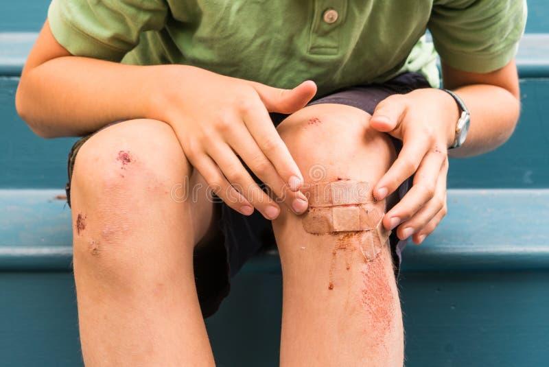 Jeune garçon sur les opérations à la maison avec les genoux ferraillés photographie stock