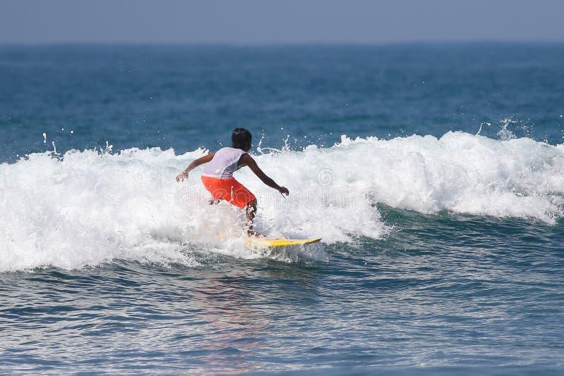 Jeune garçon surfant sur des ressacs en Californie photo stock