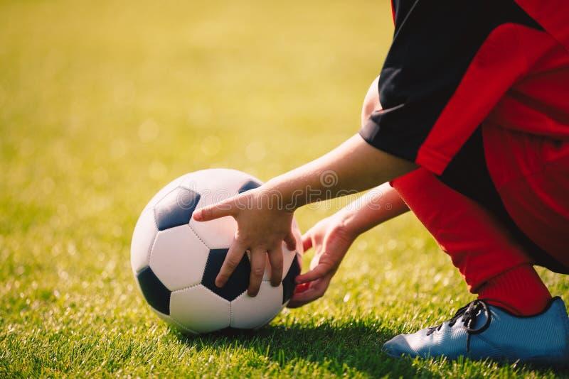 Jeune garçon tenant la boule du football Le football folâtre le fond image libre de droits