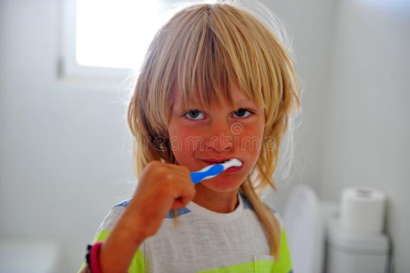Jeune garçon tenant la brosse à dents se tenant dans la salle de bains images stock