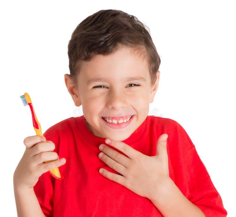 Jeune garçon tenant la brosse de dents heureusement images stock
