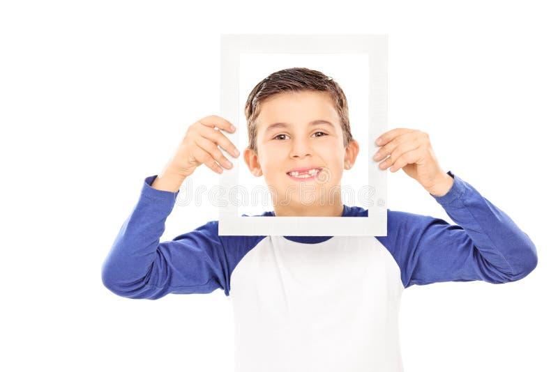 Jeune garçon tenant un cadre de tableau images stock