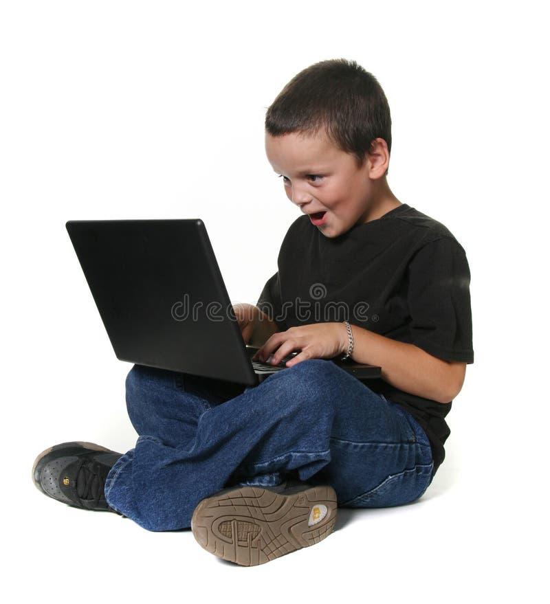 Jeune garçon travaillant sur l'ordinateur portable photos stock