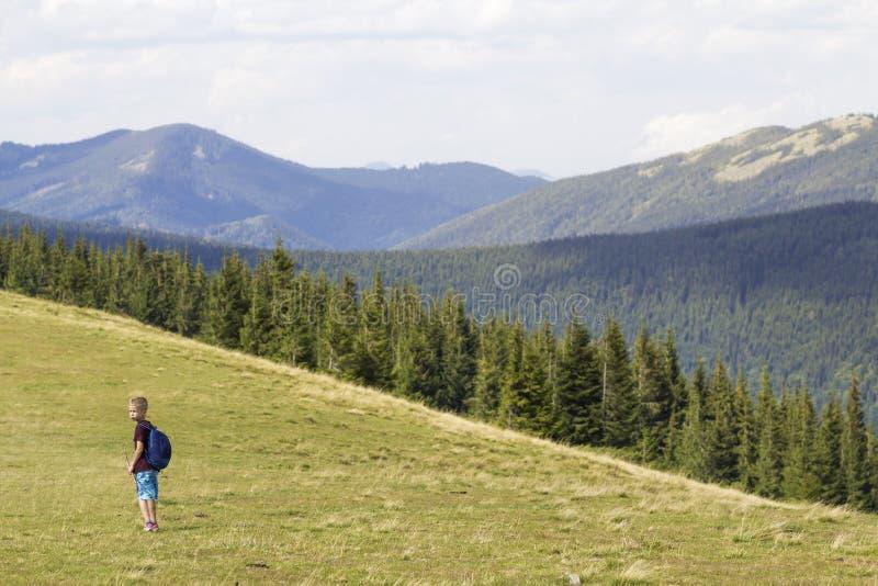 Jeune gar?on heureux d'enfant avec le sac ? dos marchant en vall?e herbeuse de montagne sur le fond de la montagne bois?e d'?t? M images stock