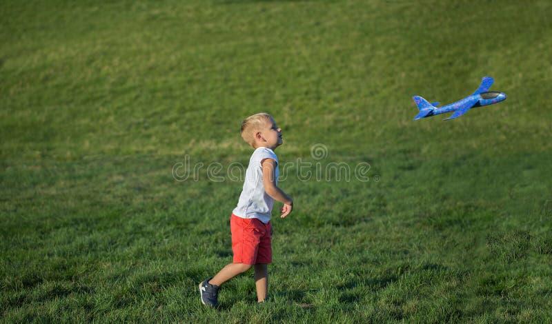 Jeune gar?on jouant l'avion sur l'herbe verte photos libres de droits