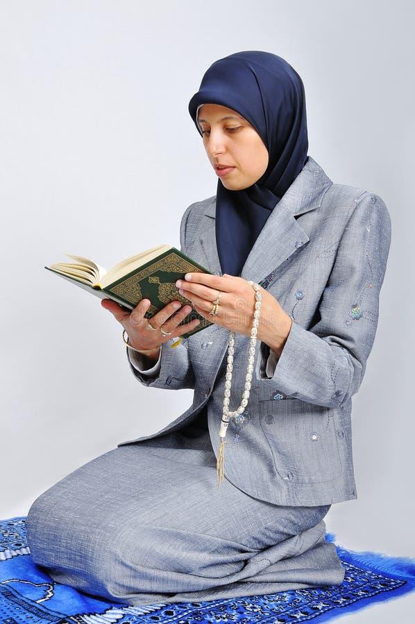 Jeune gentille femelle musulmane priant sur le wa traditionnel photo libre de droits