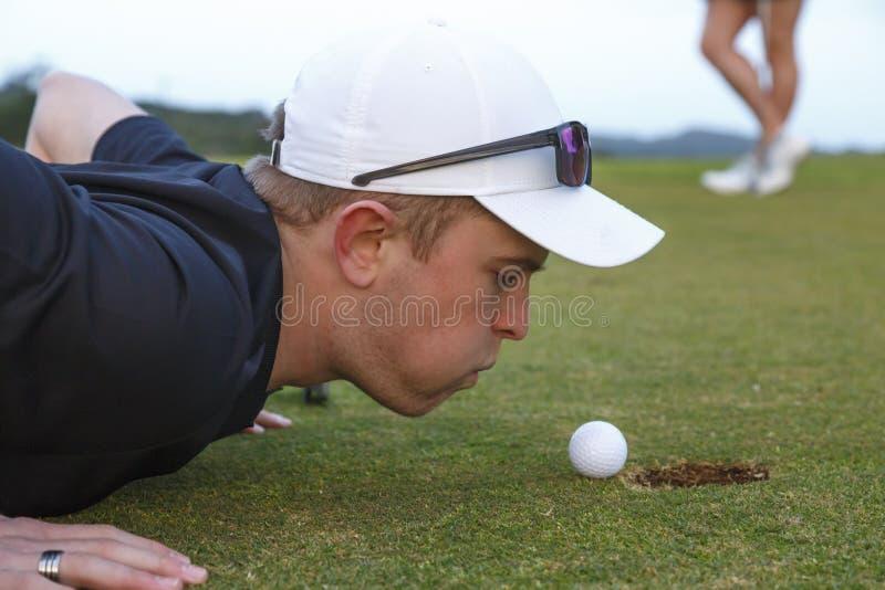 Jeune golfeur essayant de souffler la boule dans la tasse photographie stock