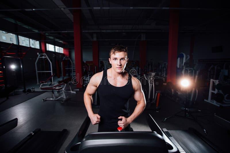 Jeune grand modèle fort de forme physique d'homme dans le gymnase fonctionnant sur le tapis roulant avec la bouteille d'eau photo stock