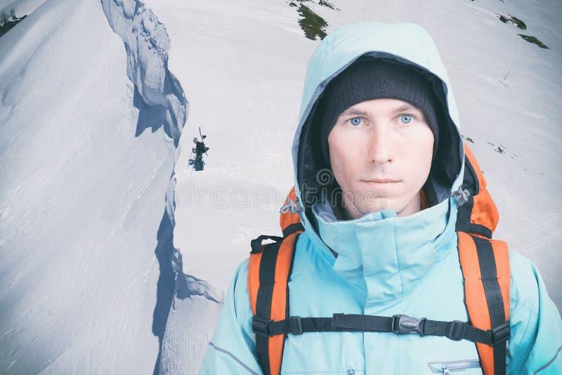 Jeune grimpeur de montagne masculin sur la vue de flanc de montagne d'hiver regardant la caméra Front View Mode de vie actif en t image libre de droits