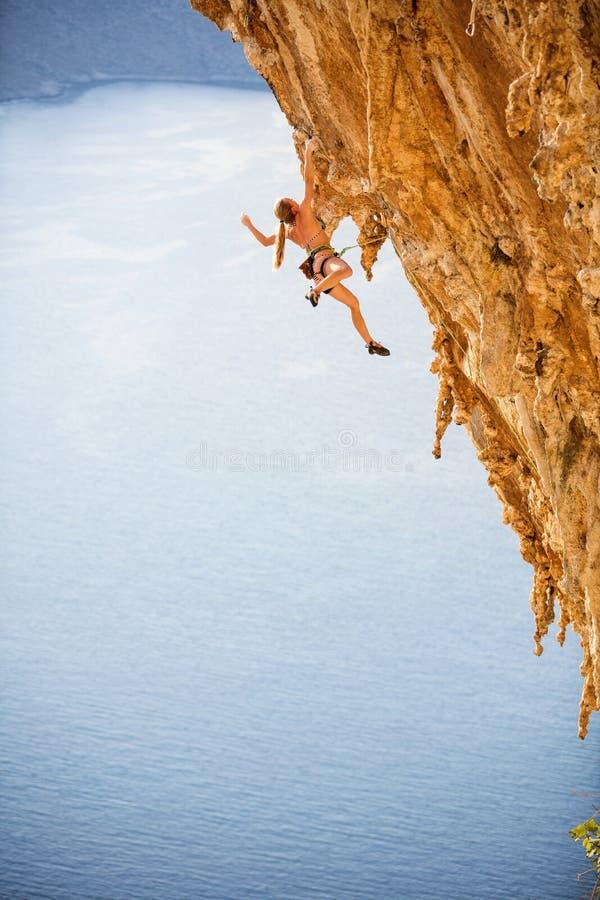 Jeune grimpeur de roche féminin dans le bikini accrochant avec une main sur la falaise image libre de droits