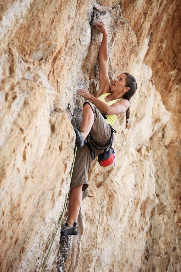 Jeune grimpeur de roche féminin sur un visage de falaise images libres de droits