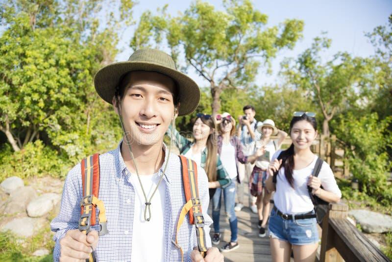 Jeune groupe heureux trimardant ensemble par la forêt photo stock
